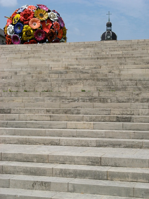 Marble Steps with a pot of plastic flowers at the top leading up to a clocktower that is partially obscured by the steps.